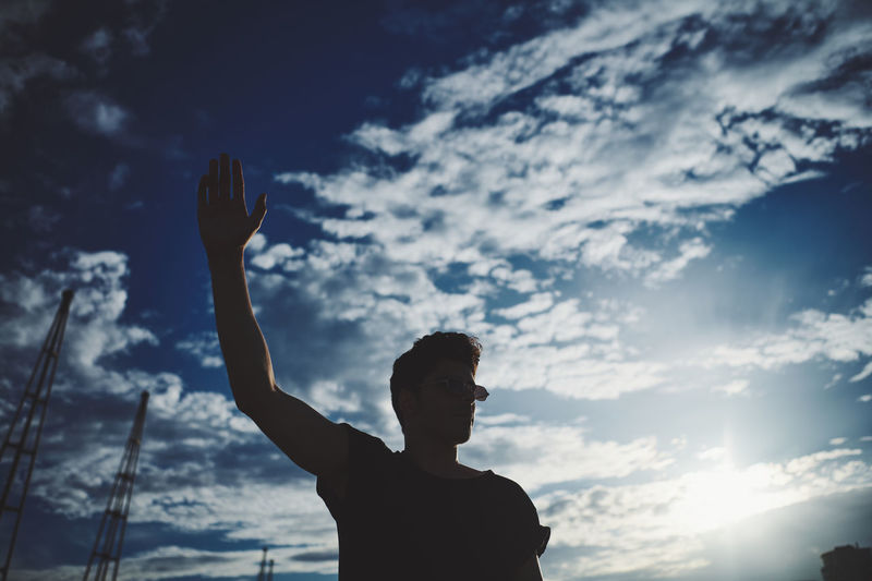 Low angle view of silhouette man standing against sky with a hand in the air