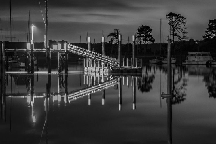 Reflection of bridge in lake against sky at dusk