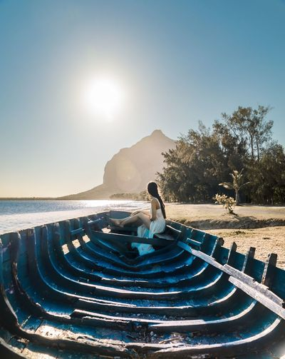 Woman Sitting On Shipwreck At Beach