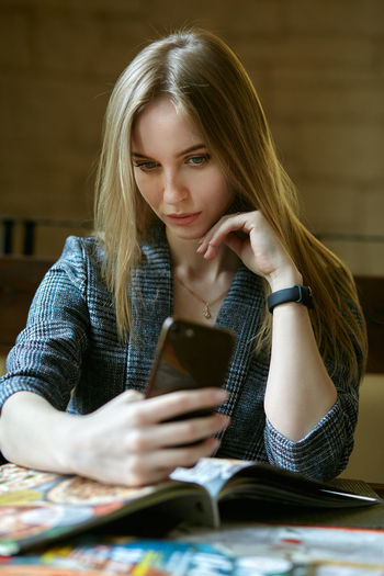 Young woman taking selfie with smart phone while sitting at table