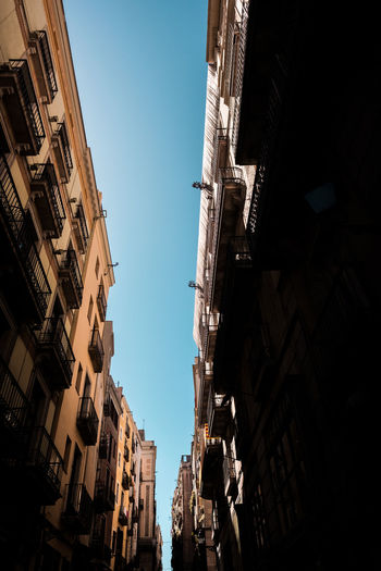 Lots of light, but even more shadow. Getting lost in the narrow streets of Barcelona, Spain. Architecture Barcelona Catalunya Old Town SPAIN Streets Summertime Travel Travel Photography Architecture Architecture Photography Blue Sky Built Structure Day Fujifilm Historic Low Angle View No People Old Buildings Old House Sky Street Street Photography Streetphotography Sunshine