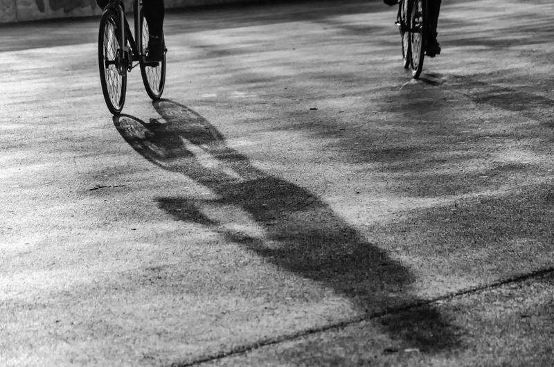 Low section of man with bicycle on shadow
