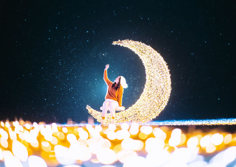 Woman standing by illuminated lighting equipment at night
