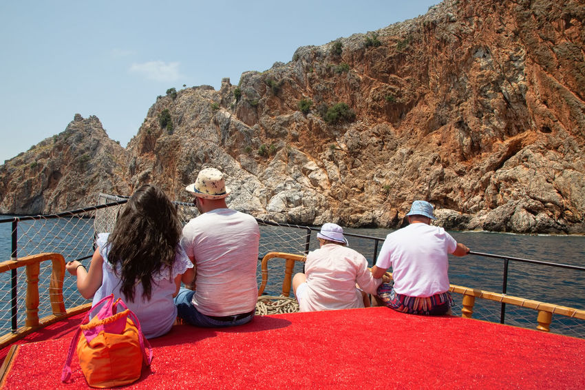 Alanya Boat Ride Mediterranean  Mediterranean Sea Turkey Alanya Castle Blue Sky Boat Tour Boatride Boats And Water Casual Clothing Formation Group Of People Leisure Activity Lifestyles Men Mountain Nature Real People Rear View Rock Scenic View Seascape Sitting Sky Togetherness Women