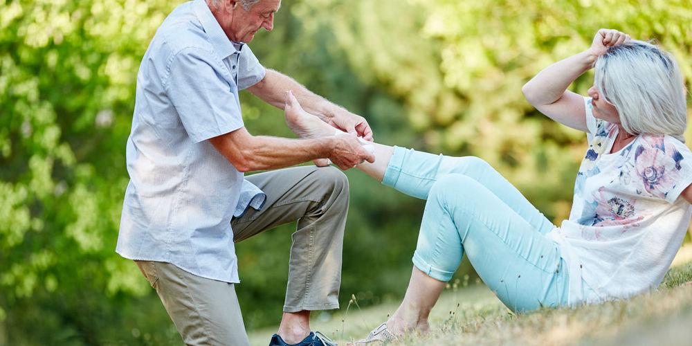 Man bandaging woman leg at park