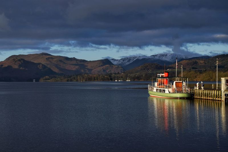 Boat moored in river by mountains against cloudy sky