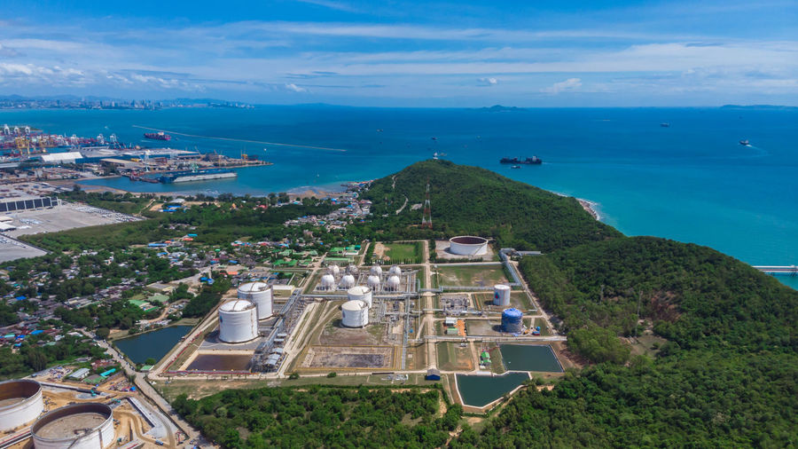 High angle view of refinery buildings area and mountain sea blue sky backgrounds