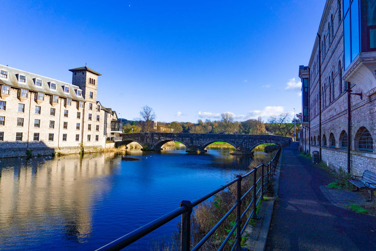 Cityscape of River Kent at Lound Road in Kendal, Cumbria, England in blue sky day Architecture Built Structure Building Exterior Water Bridge Bridge - Man Made Structure Connection City Sky River Transportation Nature Blue Travel Destinations Railing Building No People Day Arch Bridge Outdoors Footbridge