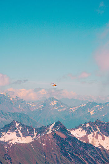 Helicopter flying over rocky mountains against blue sky