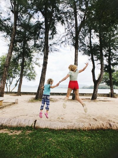 Full length rear view of woman and daughter jumping on sand