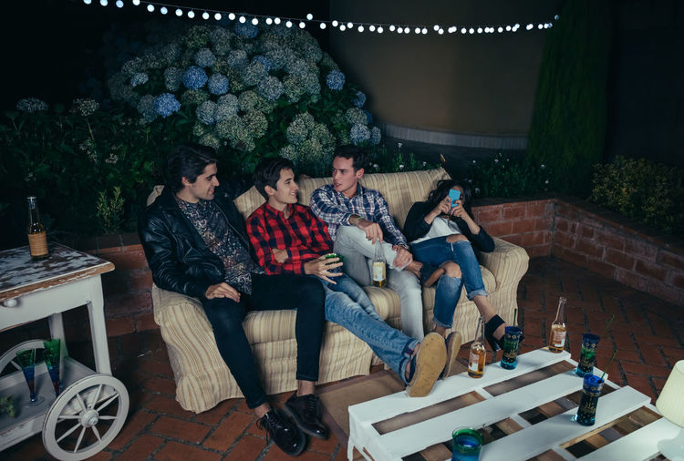 High angle view of friends sitting on sofa at patio during night