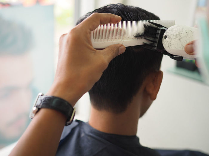 Cropped hand of barber cutting mid adult man hair