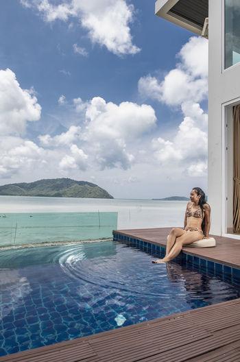 Woman relaxing in swimming pool against sky