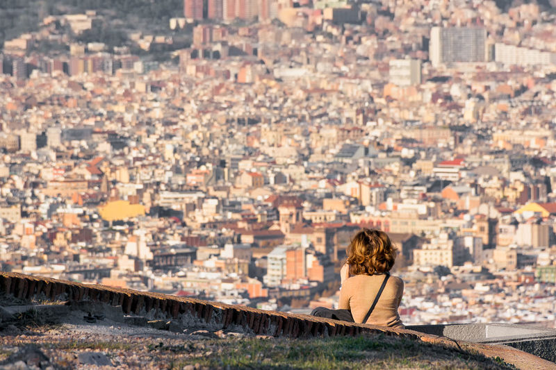 Rear view of woman looking at city buildings in barcelona