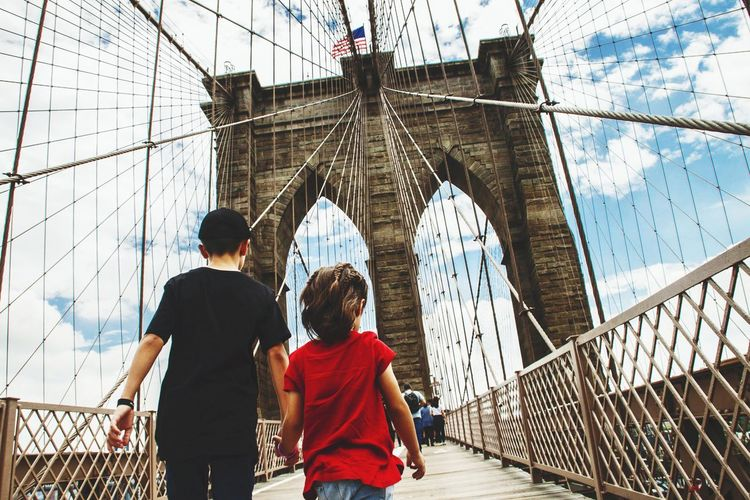 Rear view of brother and sister walking on brooklyn bridge