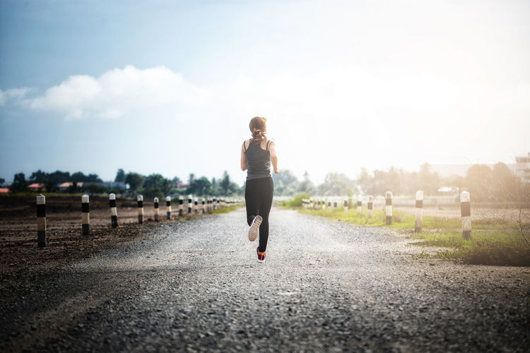 Rear view of woman running on road against sky