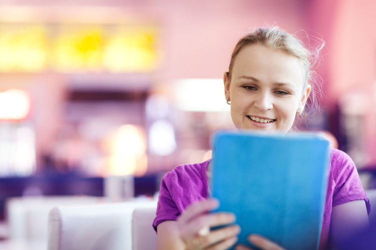 Happy young woman using digital tablet in restaurant