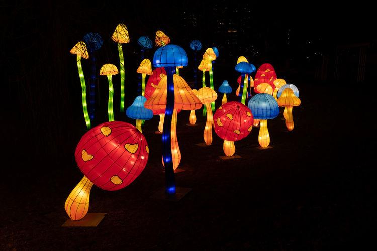 Illuminated lanterns hanging against black background