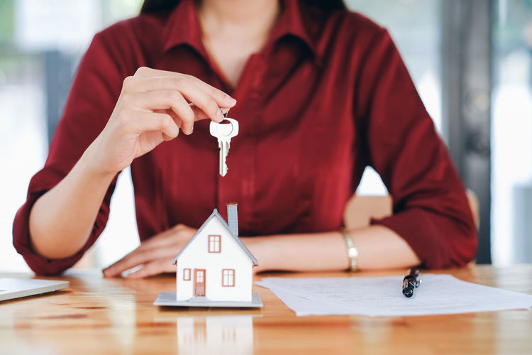 Midsection of businesswoman holding house key at desk