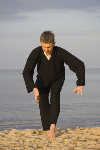 Full length of man practicing tai chi on sand at beach