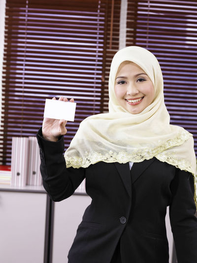 Portrait Of Smiling Businesswoman Holding Filed While Standing In Office