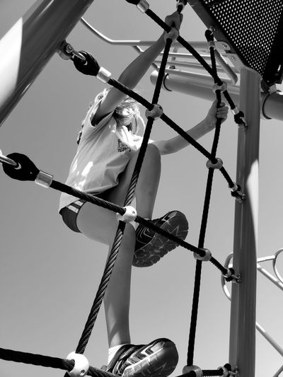 Low angle view of man climbing on rope