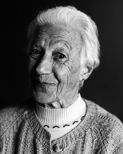 Portrait of old woman against black background