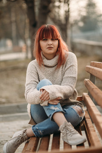 Sitting One Person Casual Clothing Redhead Women Adult Seat Young Adult Day Clothing Full Length Leisure Activity Hairstyle Wood - Material Front View Jeans Lifestyles Real People Focus On Foreground Scarf Dyed Red Hair Beautiful Woman Warm Clothing