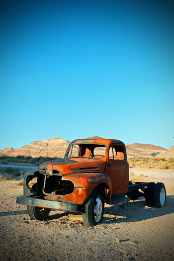 American Trucks Abandoned Arid Climate Blue Car Clear Sky Climate Damaged Day Desert Deterioration Environment Land Land Vehicle Landscape Mode Of Transportation Motor Vehicle Nature No People Obsolete Old Ruin Outdoors Sky Sunlight Transportation