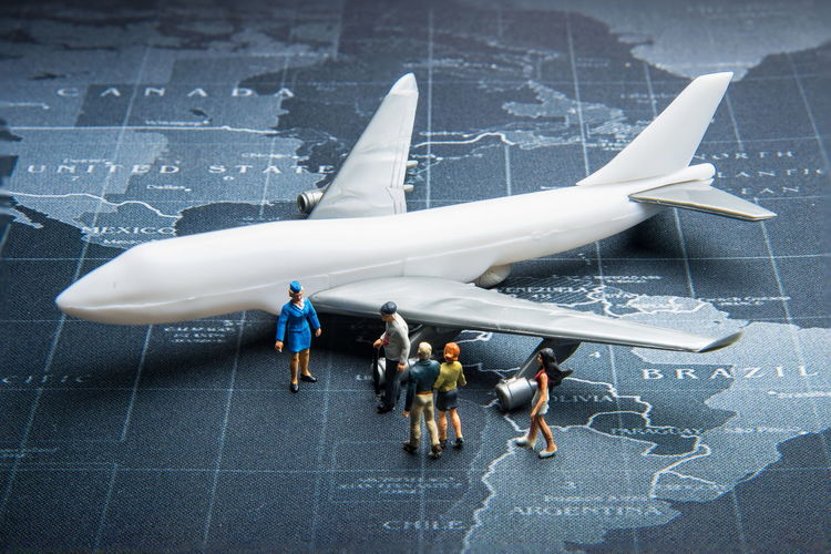 High Angle View Of Toy Airplane And Figurines On World Map