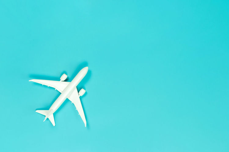 Close-up of airplane flying over blue background