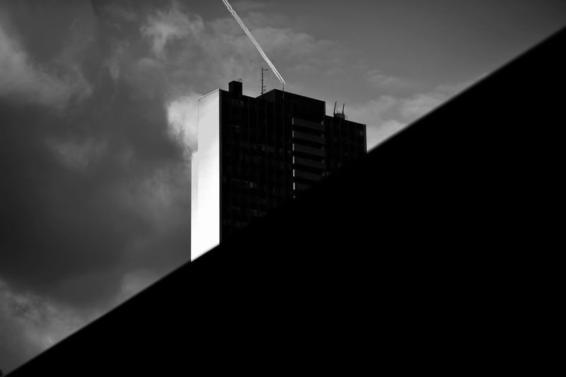 Low angle view of silhouette building against sky