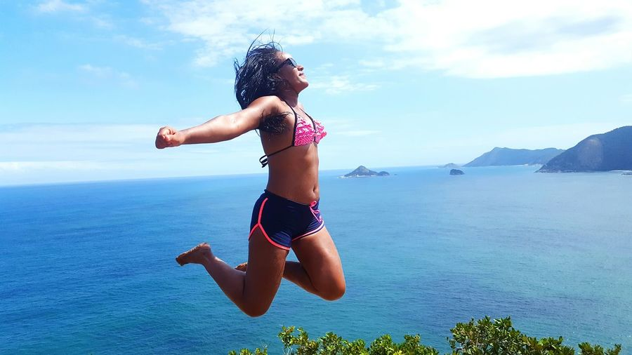 Carefree Woman Jumping Against Sea
