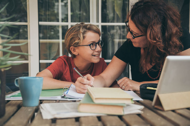 Woman teaching son studying at table