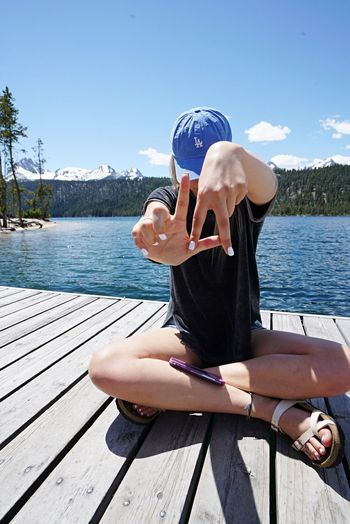 Young woman sitting on pier over lake against sky