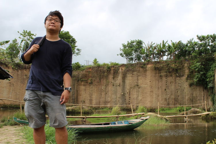 Young man standing by river against cliff