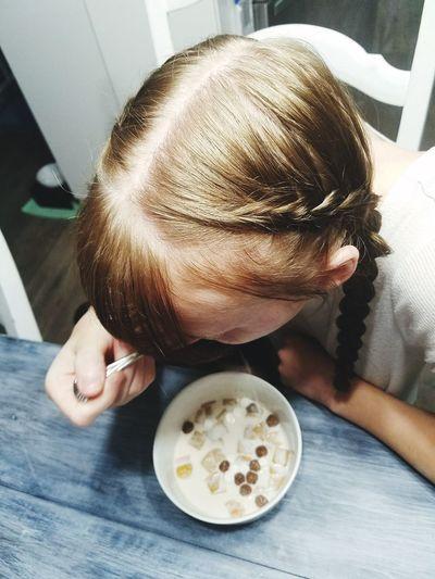 High angle view of girl eating food at home