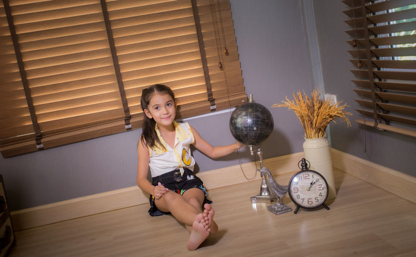 Full length portrait of cute smiling girl sitting on floor at home