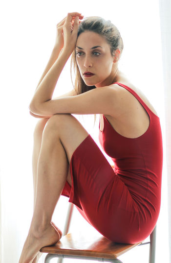 Red Red Dress Sitting Woman Adult Beautiful Woman Beauty Clothing Fashion Photography Full Length Girl Indoors  Legs Lifestyles Looking At Camera One Person Portrait Red Red Color Sitting Sitting Alone Sports Clothing Women Young Adult Young Women