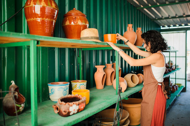 Side view of cheerful female potter standing by display in pottery shop