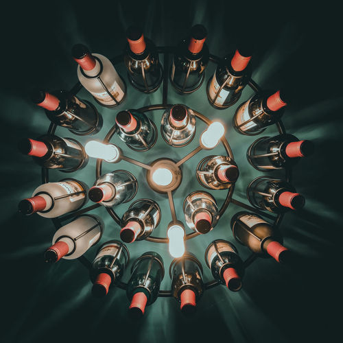 Directly above shot of illuminated lighting equipment by bottles on table