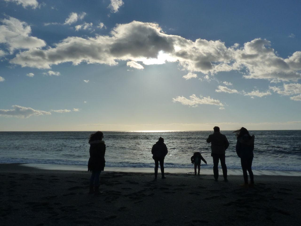 Silhouette People On Calm Beach