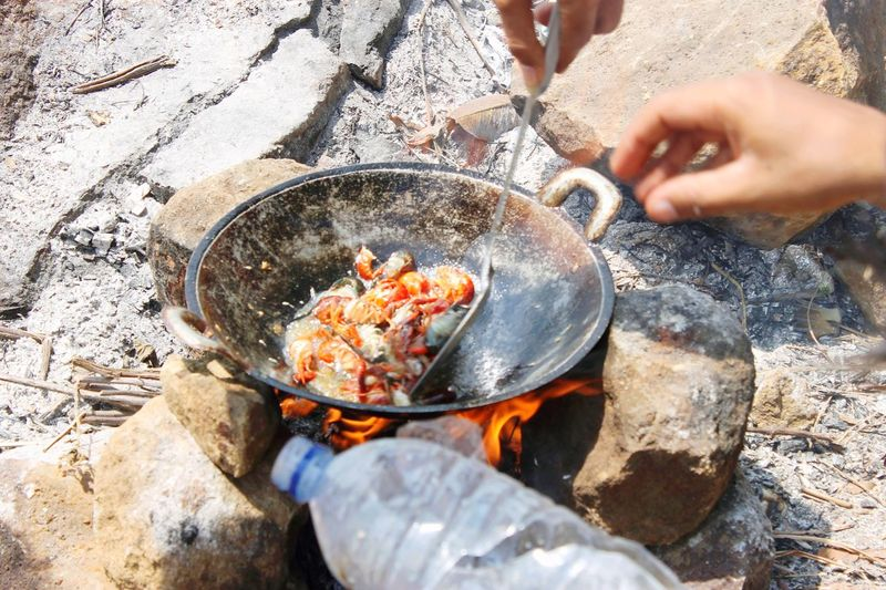 Midsection of man preparing food on rock