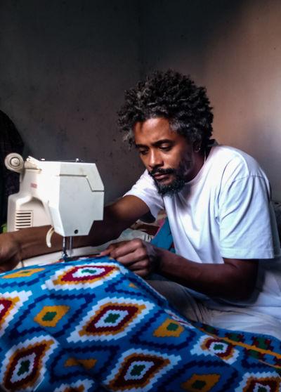 Young man sewing cloth at home