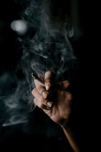 Midsection of man smoking cigarette against black background