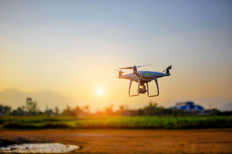 Drone flying against sky during sunset