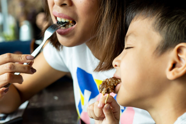 Mother and son eating food on table