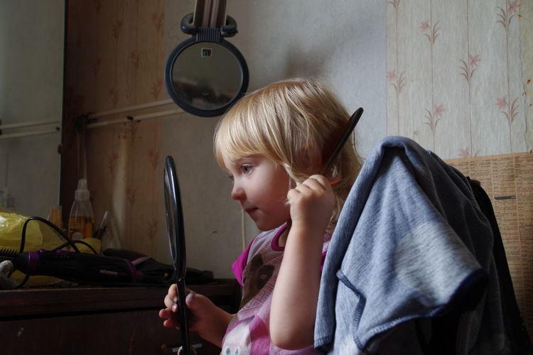 Cute girl dressing hair up looking at mirror at home