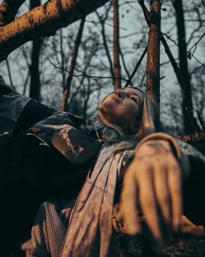 Woman lying on tree in forest