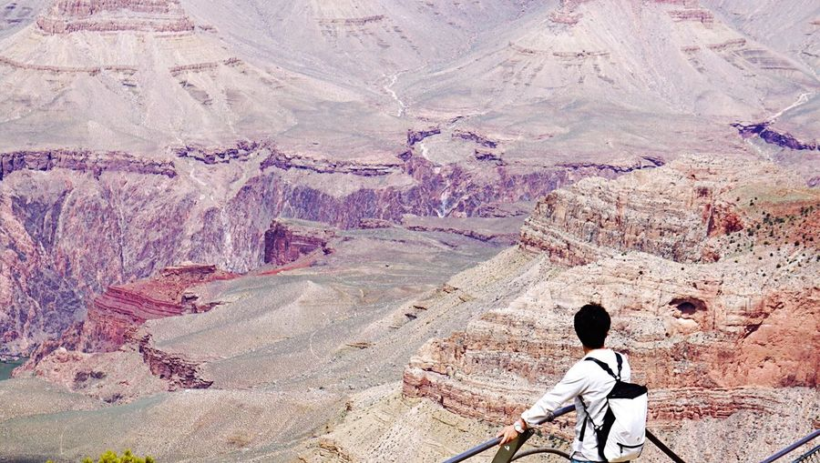Man Standing On Grand Canyon Skywalk Against Rocky Mountains